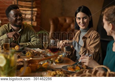 Multi-ethnic Group Of Friends Smiling Happily While Enjoying Dinner Party In Cozy Lighting
