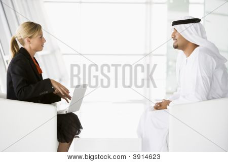 Middle Eastern Business Man And Western Woman Discussing Business