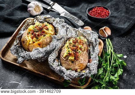 Tasty Baked Potato Topped With Cheddar Cheese, Garlic And Parsley. Black Background. Top View