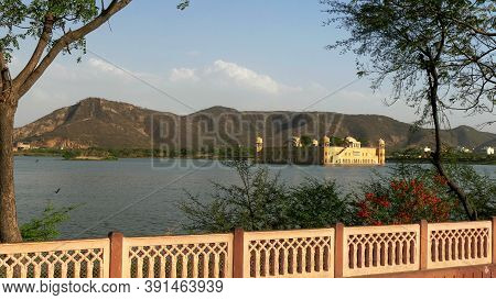 Wide Shot Of Jal Mahal Palace Framed By Trees And A Wall In Jaipur