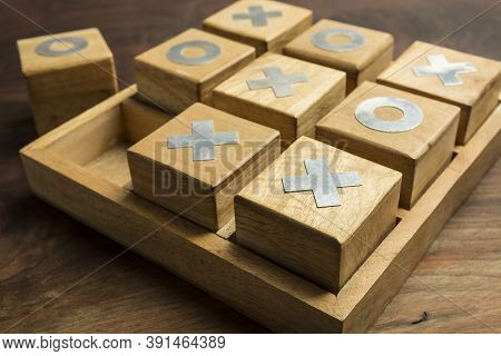 Fun Concept. Playing A Game Of Tic Tac Toe With Wooden Pieces On A Wooden Background