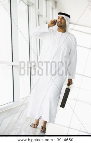 Businessman walking in a corridor on a cellular phone and smiling (high key/selective focus) poster