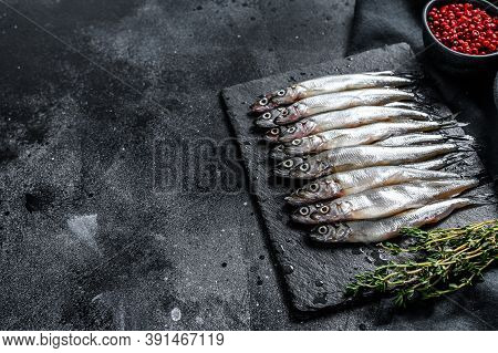 Raw Smelt With Pepper And Thyme. Black Background. Top View. Copy Space