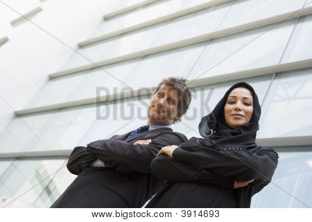 Middle Eastern Business Woman And Western Man Stood Outside Offices