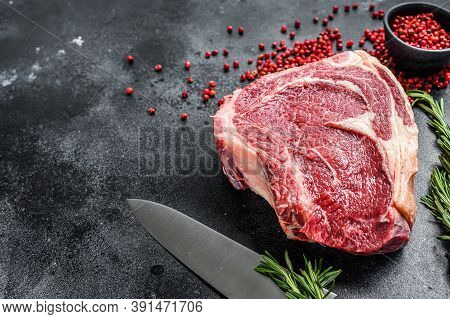 Raw Cowboy Steak Or Ribeye On The Bone With Herbs. Marble Beef. Black Background. Top View. Copy Spa