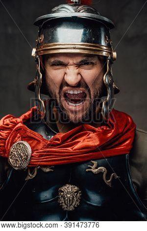 Savage Bearded Roman Soldier Dressed In Black Armour With Helmet And Red Mantle Screaming In Dark Ba