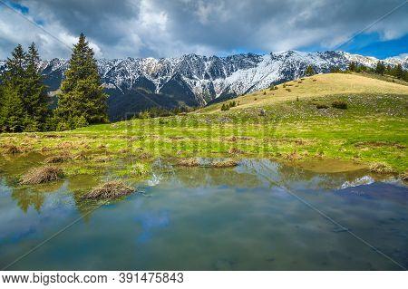 Amazing Alpine Landscape With Small Lake And High Snowy Piatra Craiului Mountains, Near Pestera Vill