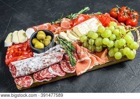 Italian Antipasto, Wooden Cutting Board With Prosciutto, Ham, Parma, Goat And Camembert Cheese, Oliv