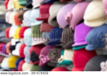 Many Collection Hat On Rack In Market. Blurred Background.