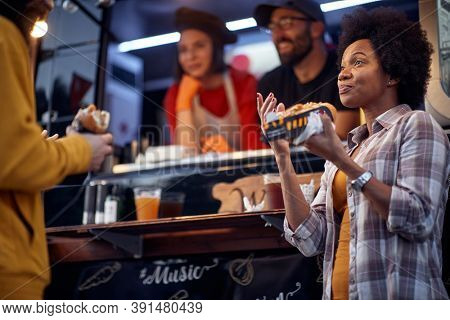 thrilled afro-american woman talking to a beardy guy while eating sandwich. two employees in the back