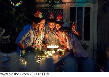 Group of cheerful friends blowing candles on the cake at the open air birthday party on a beautiful summer night. Quality friendship time together