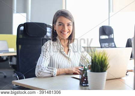 Beautiful Smiling Business Woman Is Sitting In The Office And Looking At Camera