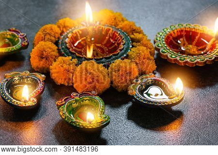 Close Up Clay Lit Light A Fire Already On Diya Or Oil Lamp With Flowers, Studio Shot On Concrete Bac