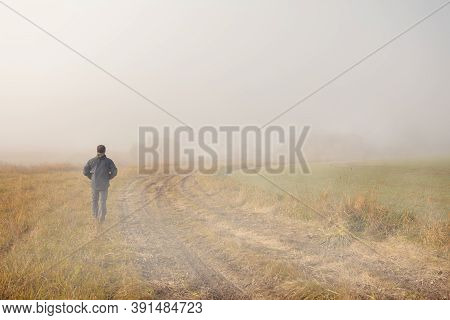 A Person Walk Into The Misty Foggy Countryside, Rural Road In A Dramatic Mystic Sunrise Scene With A