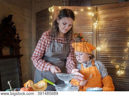 Mom And Little Son Prepare Pumpkin Pie For Thanksgiving. Concept Of Family Holidays And Traditions