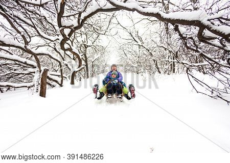 Mother With A Child Riding On A Sled. A Woman With Her Son Rides Down The Hill In A Sleigh And Screa