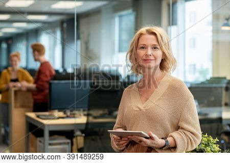 Mature blond businesswoman in casualwear standing in front of camera in large modern office and using tablet against two young colleagues