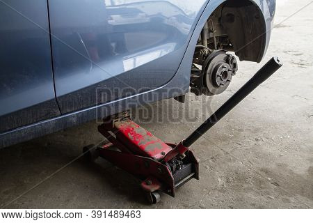 Replacing Wheels On A Car, Jack Holds The Body In Raised Position. Car Without Wheel And Lift Up By