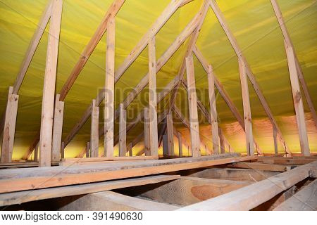 A View On Unfinished Attic From Inside The House With A Close-up On Wooden Ceiling Joists, Roof Beam