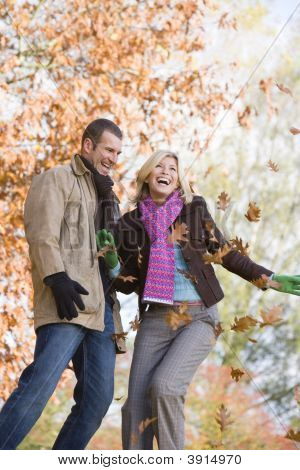 Couple Throwing Leaves Into The Air