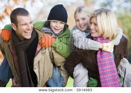 Couple With Children On Backs In Woodland