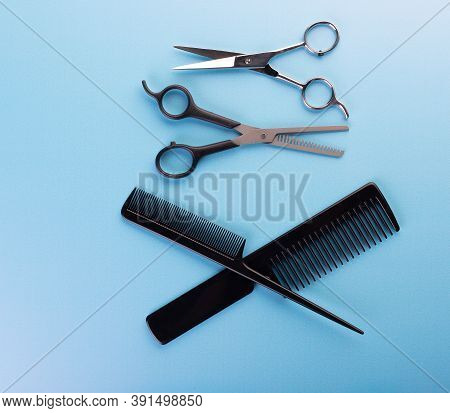 Professional Tools For Hairdresser Isolated On Blue Background: Hair Combs And Haircutting Scissors.