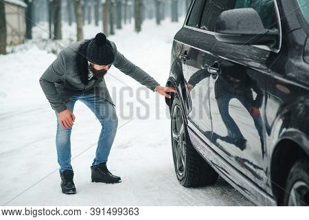 Man Checking Car Tyre In Winter. Businessman Has Problems With The Wheels Of The Car. Winter Snowy W