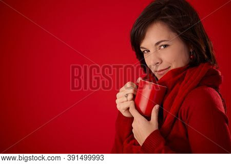 Young woman in red autumn clothes drinking tea from red mug in front of red background, looking at camera, smiling.