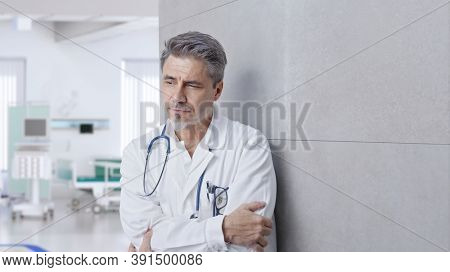 Smiling doctor on hospital corridor, Trustworthy older man with gray hair.