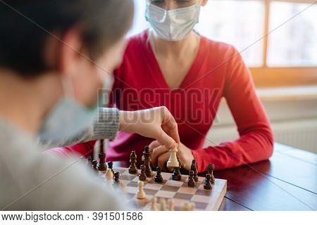 Family playing board games during curfew moving chess pieces, close-up