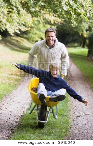 Man Pushing Boy In Wheelbarrow