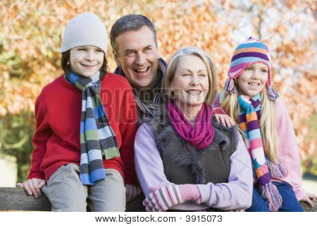 Grandparents And Children Sat On Woodland Fence