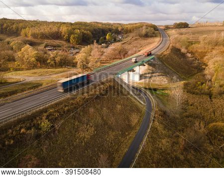 White Truck with Cargo Semi Trailer Moving on Highway Road intersection junction. Aerial Top View