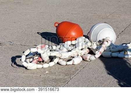 Heavily Used Small Dilapidated White Plastic Buoys Held Together By Strong Rope And Tied To Large Wh