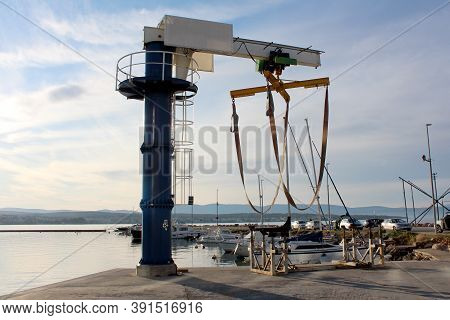 Marine Deck Boat Lifting Crane Mounted On Edge Of Concrete Pier At Local Harbor Surrounded With Calm