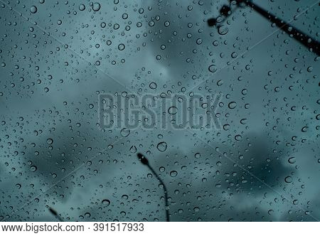 Raindrops On Transparent Glass Against Blur Dark Stormy Sky And Electric Pole. Rain Drops On Windshi