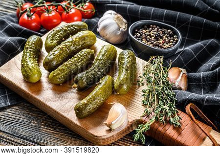 Marinated Cucumbers Gherkins On Wooden Cutting Board. Pickles With Mustard And Garlic. Black Backgro
