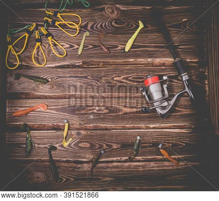 Fishing Tackle On A Wooden Background. Studio Photo With Place For Text. Spinning Rod With A Reel, S