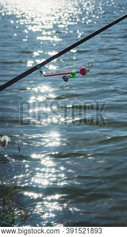 Fishing Rod With A Bell On The Lake In Autumn Against The Background Of Sun Glare On The Water. Tone
