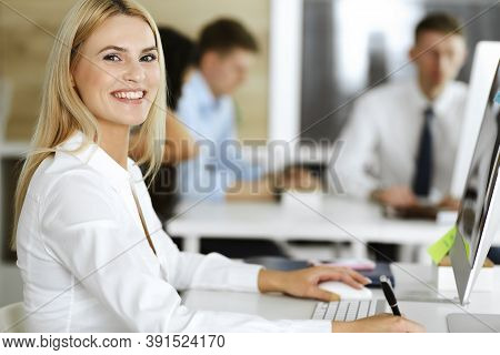 Business Woman Using Computer At Workplace In Modern Office. Secretary Or Female Lawyer Smiling And