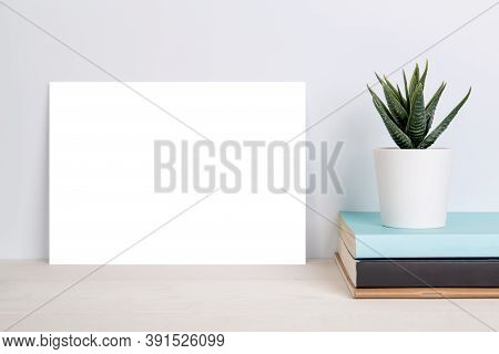 Blank Mockup Paper Sheet Copy Space And Plants In Potted On Book On Wooden Table, Poster And Invitat