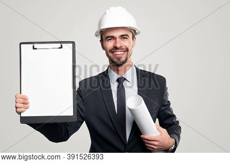 Happy Man In Suit And Helmet Carrying Rolled Up Blueprint And Demonstrating Blank Clipboard During W