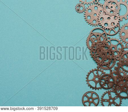 Copper Various Cogs On A Blue Background, Copy Space