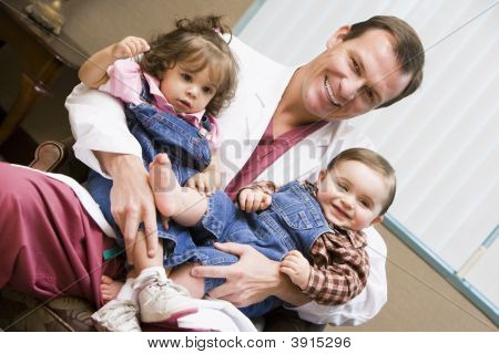 Doctor sitting with two IVF children smiling poster