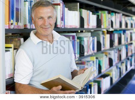 Homem sênior na biblioteca com o livro