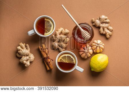 Natural Cold And Flu Home Remedies: Hot Tea Cups With Lemon, Honey, Ginger And Garlic To Boost Immun