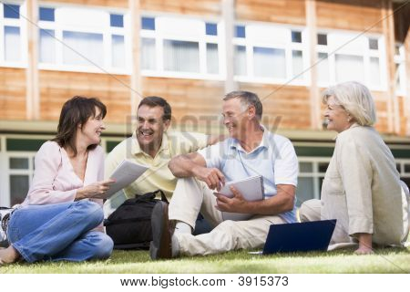 Adult students on lawn of school studying and talking poster