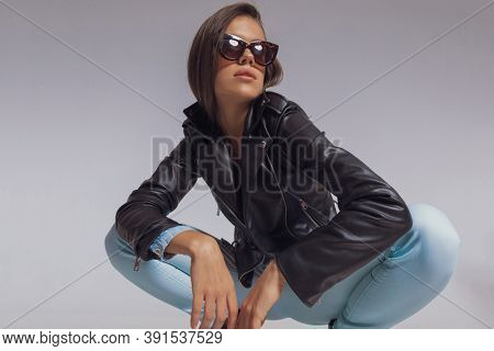 Confident fashion model looking away while wearing leather jacket and sunglasses, crouching on gray studio background