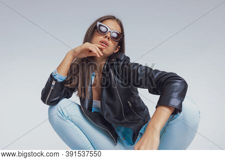 Charming fashion model holding hand on chin, wearing sunglasses and leather jacket, crouching on gray studio background