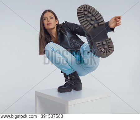 Young fashion model kicking, wearing leather jacket while crouching on gray studio background